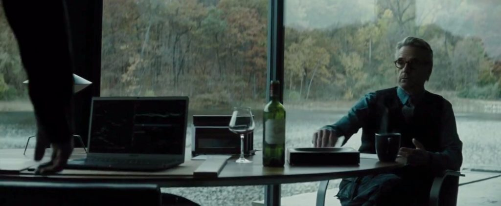Alfred seated a Bruce Wayne's desk where we see a Baccarat win glass