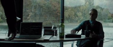 Alfred seated at Bruce Wayne's desk where we see a Baccarat wine glass