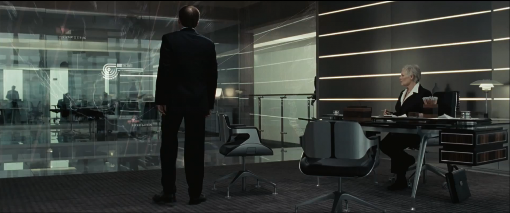 Judi Dench as M in Quantum of Solace sitting in an Interstuhl Silver Chair with two low backed Conference versions in front of her desk