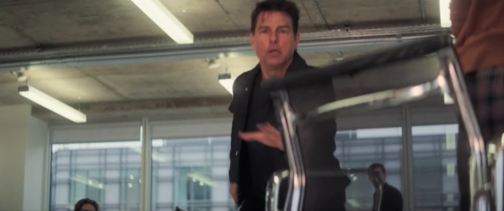 Tom Cruise reaches for the Eames office/management chair in Nero Netweave (black mesh)