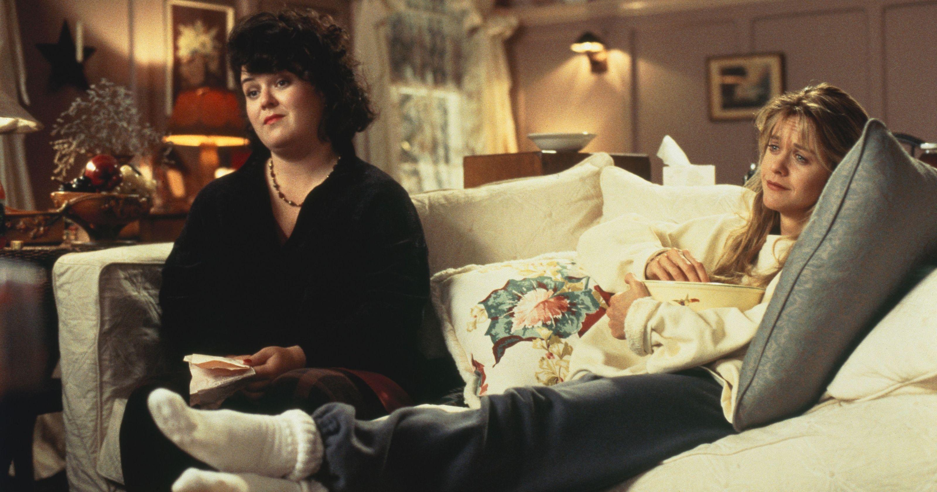 Annie ed un'amica sono sedute sul divano. Vestono abiti comodi e sembra stiano guardando un film.