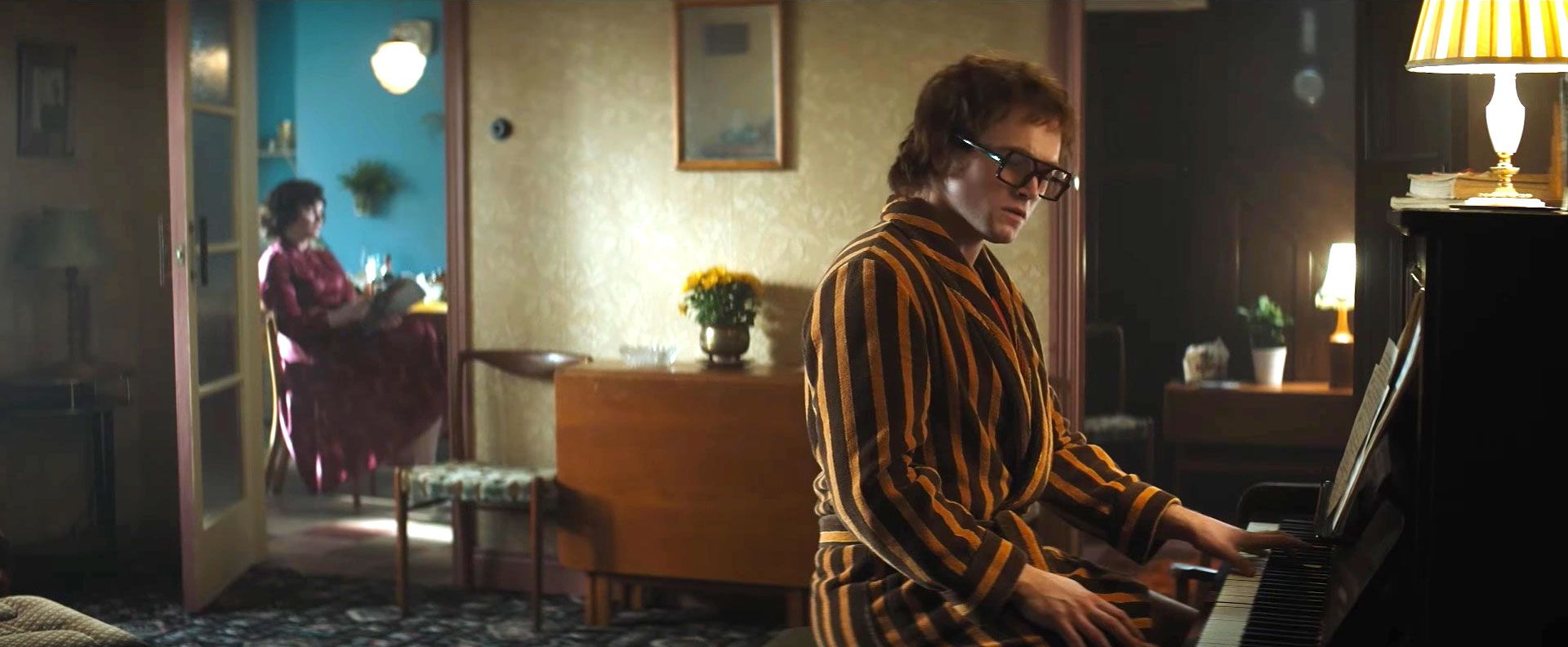 Taron Egerton as Elton John playing piano in his parents house in Rocketman filmsets