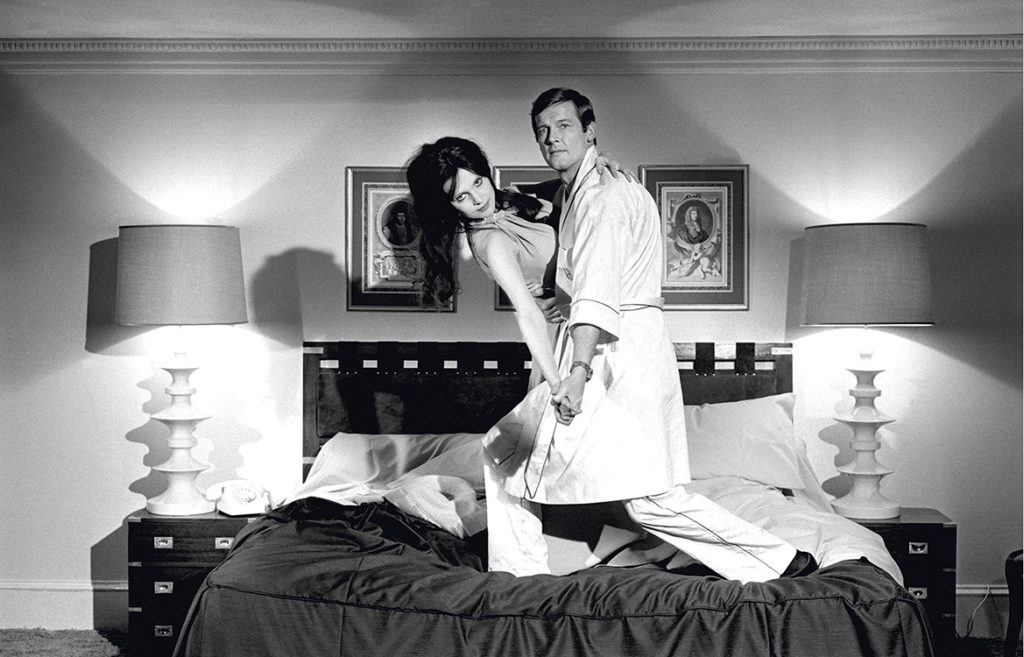Roger Moore as James Bond and Madeline Smith as Miss Caruso posing on bed on the film set of 'Live and Let Die', 1973